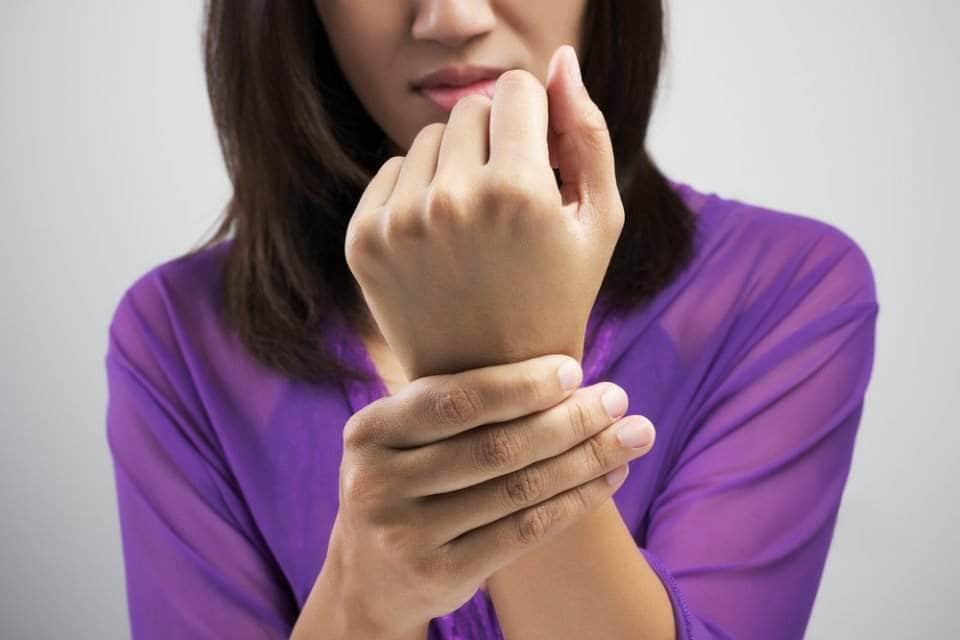 امرأة تمسك كفها ألماً