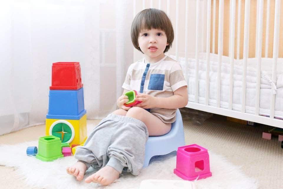 طفل يستعمل كرسي المرحاض