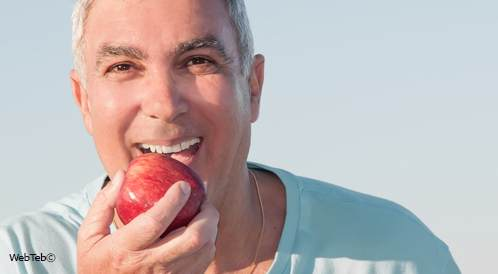 رجل كبير في السن يقضم تفاحة