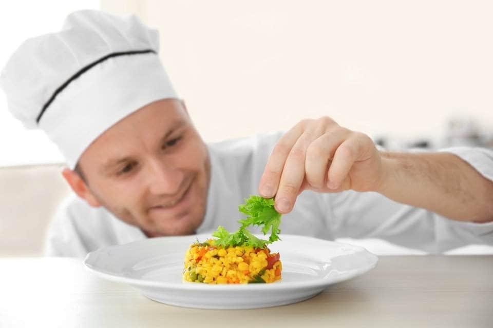 طباخ يضع الخس ويزين به طبق من سلطة الذرة