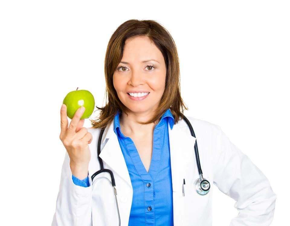 صورة طبيبة تحمل تفاحة خضراء بيديها