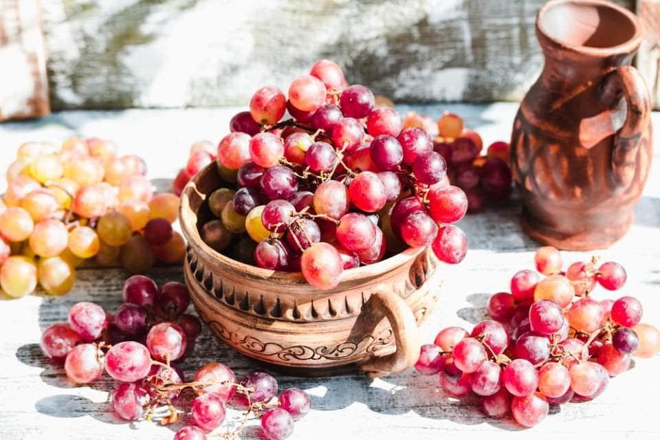 وعاء يحوي قطف من العنب الاحمر
