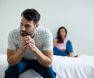 صورة لرجل حزين وزوجته في الخلفية