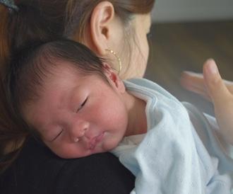 صورة لأم تضم طفلها نحو صدرها