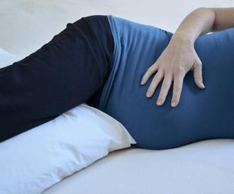صورة لإمراة حامل تضع وسادة بين قدميها