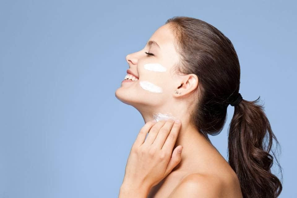 صورة لإمرأة تضع كريم على بشرتها
